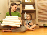 Smiling woman with little daughter sitting near cupboard holding towels in laundry room