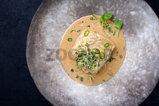Gourmet fried skrei cod fish in Thai curry with chili and sprouts as top view on a modern design plate with copy space left