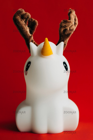 Unicorn with deer fluffy horns in red background. Funny surreal christmas art