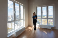Girl realtor with a folder stands at the big windows of a spacious apartment