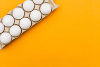 Chicken eggs in a cardboard tray. Egg tray on a colored background. Copy space.