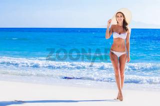 Girl in bikini and sunhat on beach