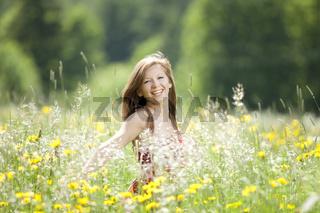 Lachende junge Frau tanzt in einer Wiese
