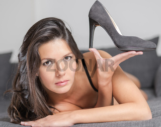 Attractive woman holding up an elegant shoe, beauty and fashion concept