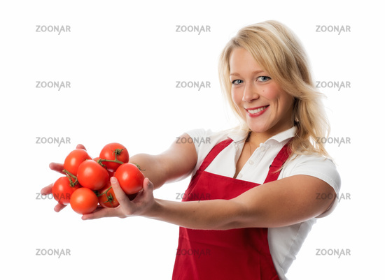 blond woman presents a handful of tomatoes