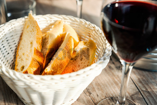 Baguette slices in basket and a glass of red wine
