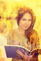 Beautiful girl with a pensive look holds a book, tree branches, a double exposure