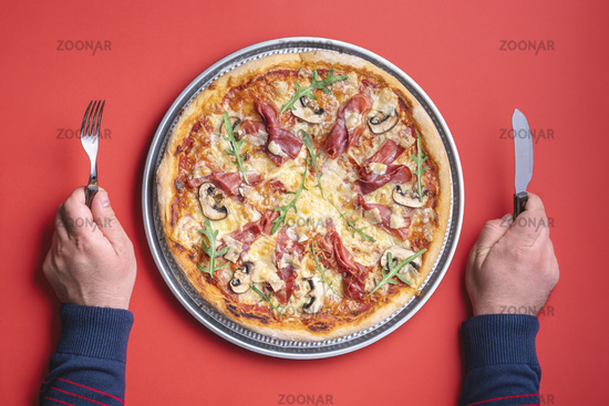 Italian pizza with prosciutto, top view. Man hands holding knife and fork