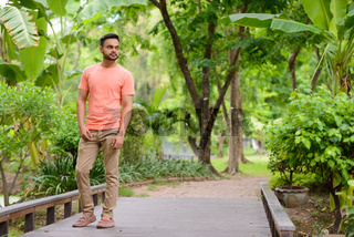 Young handsome bearded Indian man at the park