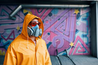 Graffiti painter in respirator mask standing near the wall with his paintings