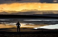 Hiker man silhouette standing at golden sunset over mountains, river and lake. Fantastic view. Iceland.