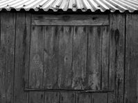 blocked up window with weathered planks on a rustic shed or farmhouse outbuilding with a tine roof