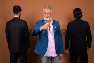 Three multi ethnic bearded businessmen together against brown background