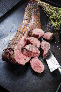 Barbecued dry aged venison tenderloin fillet steak natural with herbs and cranberry sauce offered as top view on a rustic metal tray
