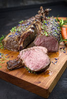 Barbecue rack of lamb with carrot and herbs offered as closeup on a modern design wooden board