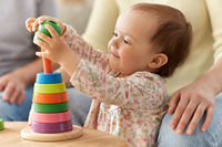 happy baby girl playing with toy pyramid at home