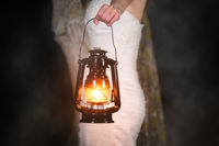 Unrecognizable Woman with Vintage Lantern Outside at Night. Young woman in white long dress walking in night wood.
