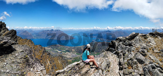 Wanderin sitzt auf Felsen der Bergkette The Remarkables, Queenstown, Südinsel, Neuseeland, Ozeanien.