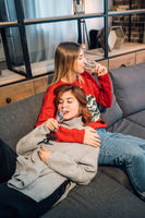 Two friends talking sitting in a couch in the living room