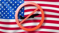 Warning sign with crossed out plane on the background of American flag.