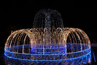 Beautiful fountain of colored holiday garlands glittering and flashing in city park in winter