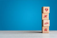 Travel health car and home personal insurance icons on wood blocks with blue backdrop - Conceptual i
