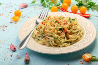 Linguini pasta with parsley and chili flakes.