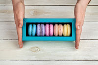 Female hands holding box with macaroons