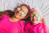 Top view woman and girl faces with cucumber slices on eyes