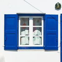 Window of a greek house with blue shutters