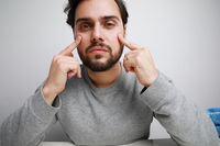 Handsome bearded young man touching his face, skin care. Isolated.