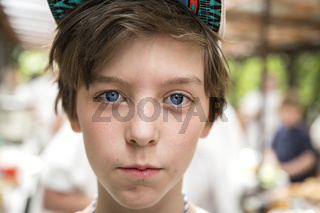 young boy with basecap looking into the camera, blurred people in background