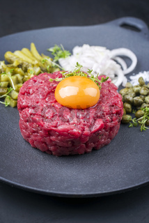 Gourmet tartar raw from beef fillet with yellow of the egg and gherkin with capers and onion rings as closeup on modern design plate