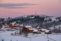 Small and quiet alpine village and winter sunrise snowy mountains around, Voronenko, Carpathian, Ukraine.