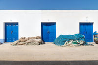 Harbour warehouse building with blue doors and heap of fisher nets, Altea, Costa Blanca, Spain