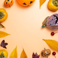 Halloween concept. Pumpkin and autumn leaves, sweet persimmon fruit on orange background. flat lay, top view, copy space