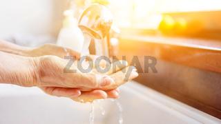 Seniorin beim Händewaschen mit Seife unter Wasser