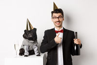Small black dog wearing party hat and standing near happy man celebrating holiday, owner showing thumb-up and holding champagne bottle, white background