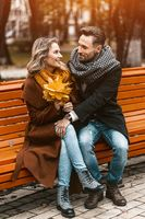 Front view of a couple in love sitting on the bench hugged in park wearing coats and scarfs collecting a bouquet of fallen leaves. Love story concept. Tinted image