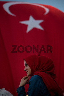 Turkish Muslim Woman with red headscarf with Turkish flag behind attending a pro government rally in