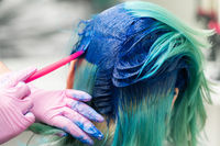 Side view of process of dyeing hair in unique color. Hairdresser in glove using pink brush while applying blue paint to customer with emerald hair color