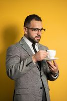 Handsome bearded man in eye glasses in formal wear holding a cup of coffee isolated on yellow background