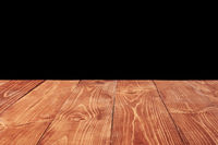 Aged natural wooden table for montage and present your products on a black background.