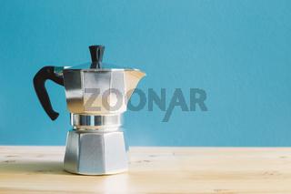 Italian metallic coffee maker Mocha coffee pot on wooden table