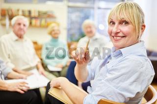 Lächelnde Frau als Psychotherapeutin oder Ärztin mit einer Gruppe Senioren