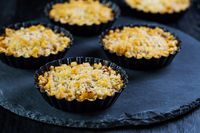Small and delicious apple pies or apple crumble on black background. Apple tart.