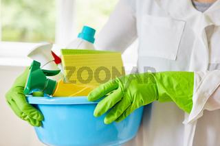 Reinigungskraft mit Handschuhen trägt Putzmittel