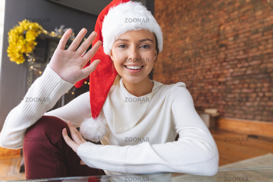 Portrait of woman in Santa hat waving at home