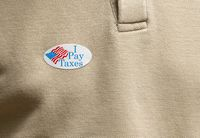 I Pay Taxes paper sticker on shirt to illustrate voter angry about rich people nto paying their share
