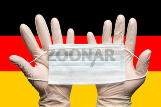 Doctor holding medical face mask in two hands in white gloves on background flag of Germany